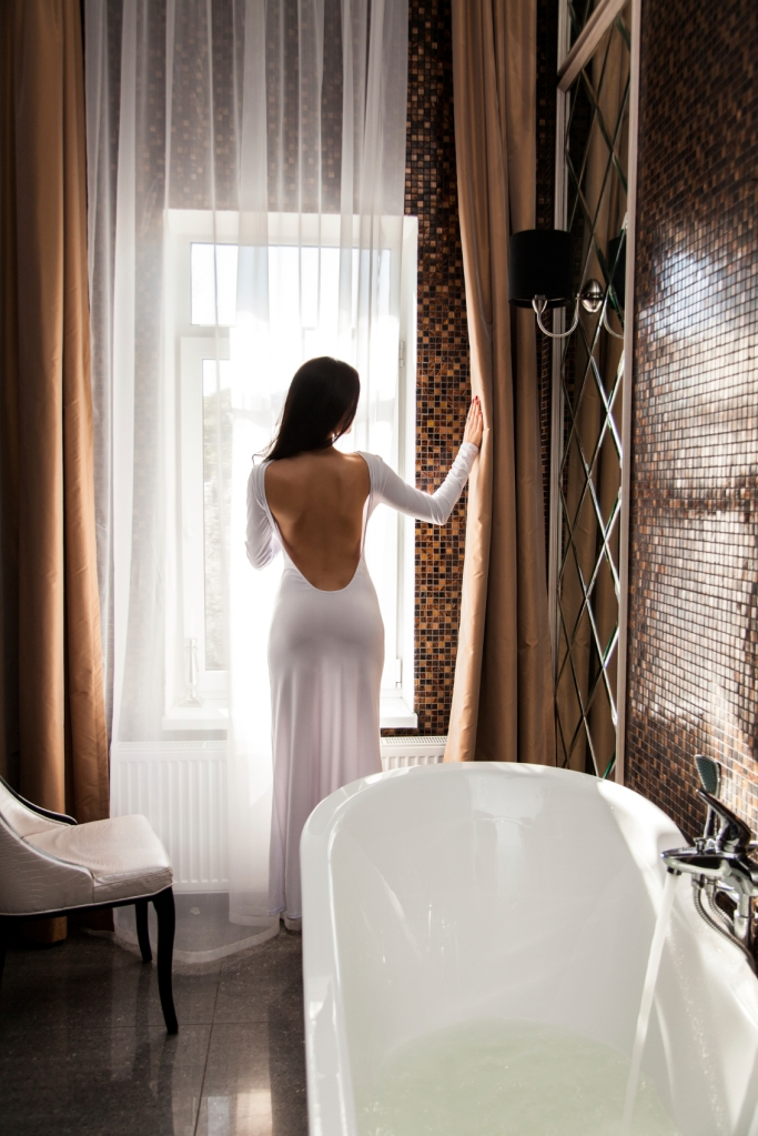 Beautiful woman open the curtain and preparing to take a bath
